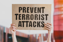 """The Question """" Prevent Terrorist Attacks """" Drawn On A Carton Banner In Men's Hand. Human Holds A Cardboard With An Inscription. Murder. Killings. Violent. Act Of Terrorism"""