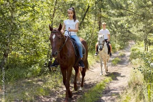 Fototapeta Group of teenagers on horseback riding in summer park obraz