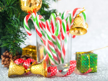Christmas Candy Sticks On Glass With Silver Bokeh Background.