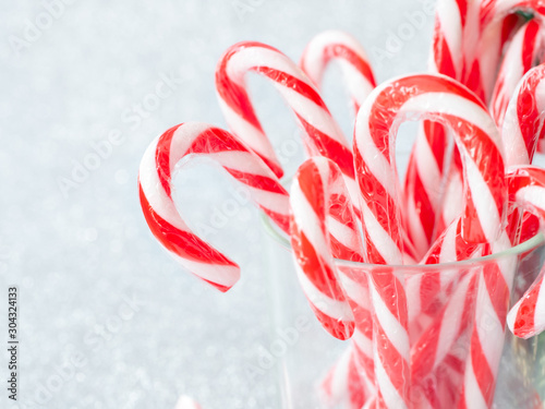 Fotografija Christmas candy sticks on glass with silver bokeh background.