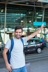 Front view of smiling traveler waving hand near airport. Cheerful young man trying to stop car. Travel concept