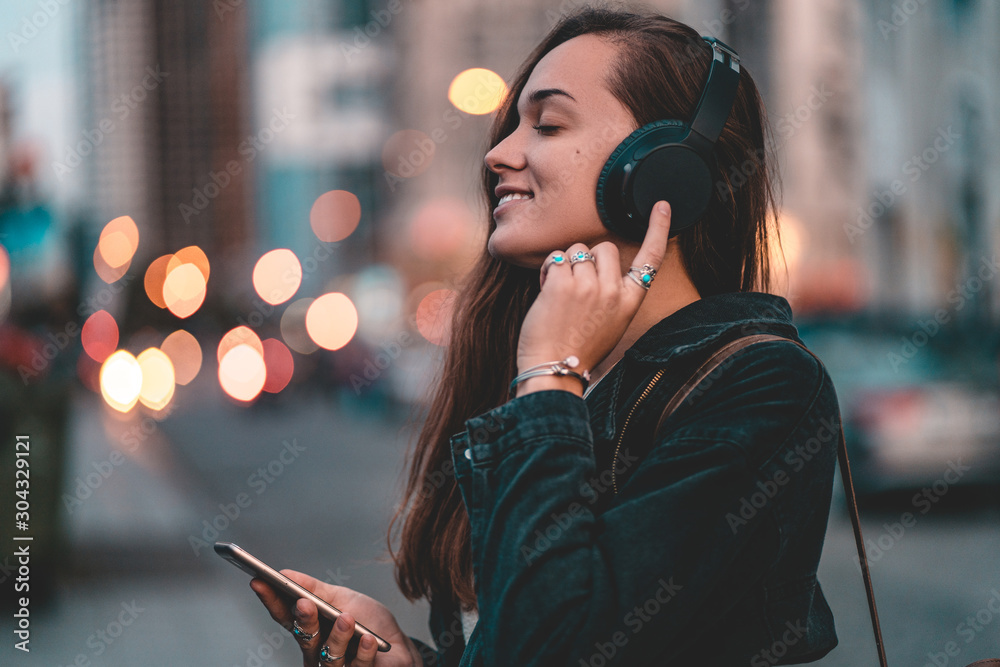 Fototapeta Young happy stylish trendy casual hipster woman teenager listening to music on a black wireless headphone while walking around the city. Music lover enjoying music