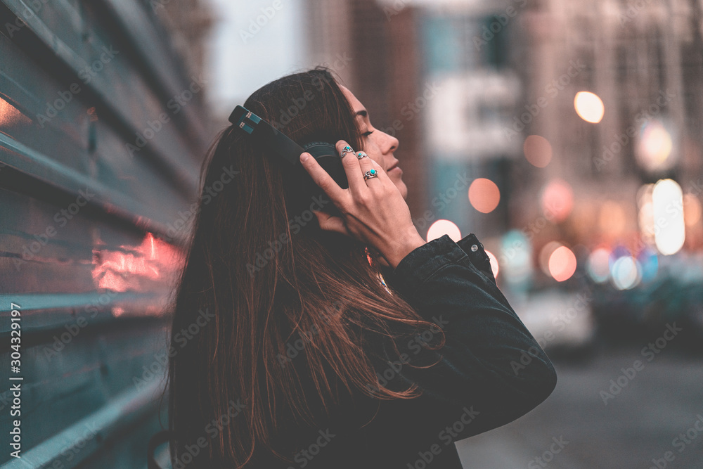 Fototapeta Young happy stylish trendy casual hipster woman teenager listening to music on a wireless headphone while walking around the city. Music lover enjoying music