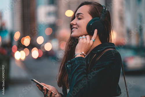 Young happy stylish trendy casual hipster woman teenager listening to music on a black wireless headphone while walking around the city. Music lover enjoying music
