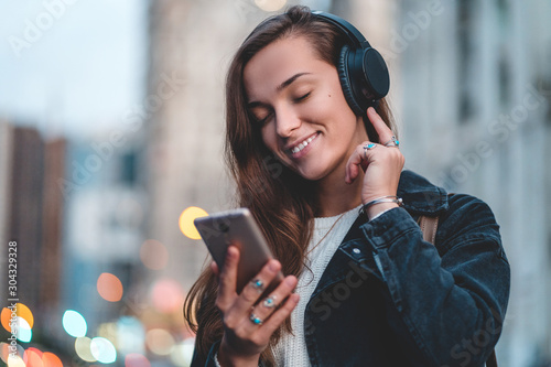 Fotografia Young happy stylish trendy casual hipster woman changes songs and tracks on smartphone during listening to music on a wireless headphone while walking around the city