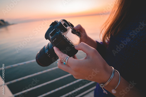 Cuadros en Lienzo  Woman photographer holds dslr camera during taking photos sea at sunset