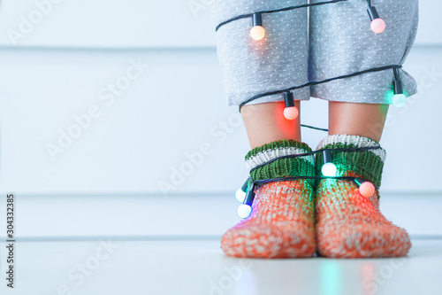 Fotografía  Female legs in warm knitted soft cozy christmas socks and garland with illuminated lights in wintertime at home
