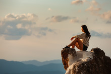Sporty Girl Sits On Big Rock A...