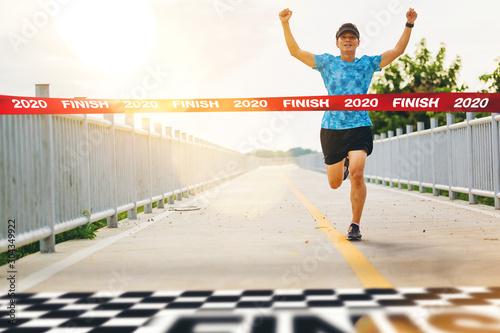 Obraz na plátně Excited man runner crossing the 2020 finish line of marathon
