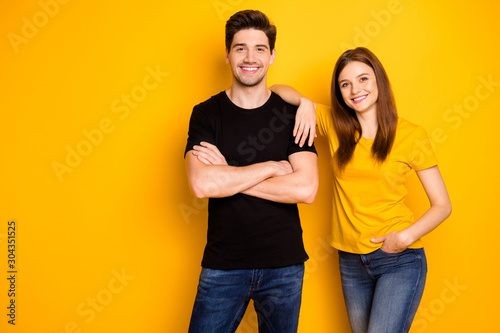 Obraz Photo of cheerful nice cute pretty beautiful couple of two people standing confidently in black t-shirt jeans denim arms crossed hand in pocket smile toothily isolated vibrant shiny color background - fototapety do salonu
