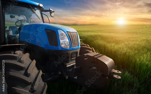 Photo Modern tractor on a field with green wheat at sunset.