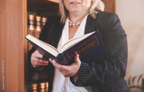 Fototapeta Avvocato donna appoggiata alla libreria che legge un libro  obraz