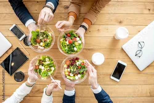Foto Office workers during a business lunch with healthy salads and coffee cups, view