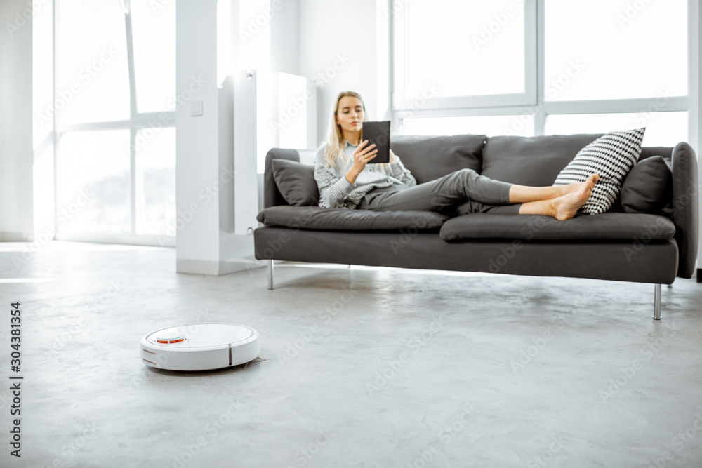 Fototapeta Woman relaxing on the couch while automatic vacuum cleaner doing the housework in the modern white living room. Household robots concept