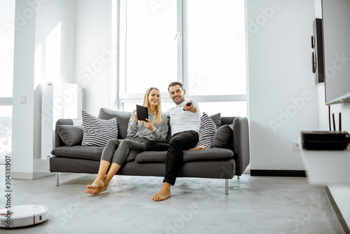 Photo Young couple relaxing on the comfortable couch, watching television in the brigh