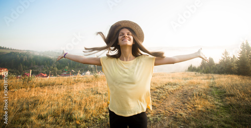 Young carefree woman enjoying nature and sunlight in straw hat on top of hill