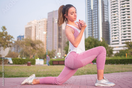 Canvas-taulu Young sporty woman stretching arms while doing lunge in the city park