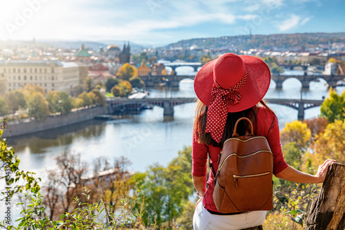 Obraz Touristin mit Hut genießt die Aussicht auf die Karlsbrücke und die Altstadt von Prag, Tschechiche Republik, an einem sonnigen Herbsttag - fototapety do salonu