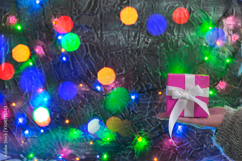 Fototapety, obrazy: Hand with a pink gift box on a background of holiday lights.