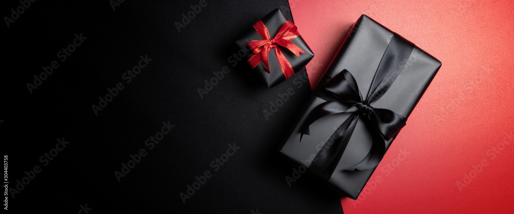 Fototapeta black gift box with black ribbons isolated on black background