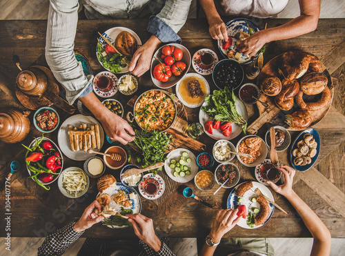 Fototapeta Turkish breakfast. Flat-lay of Turkish family eating traditional pastries, vegetables, greens, cheeses, fried eggs, jams and tea in copper pot and tulip glasses over rustic wooden background, top view obraz