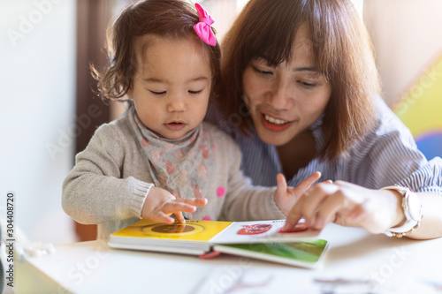 Mother and daughter reading a book together Fototapet