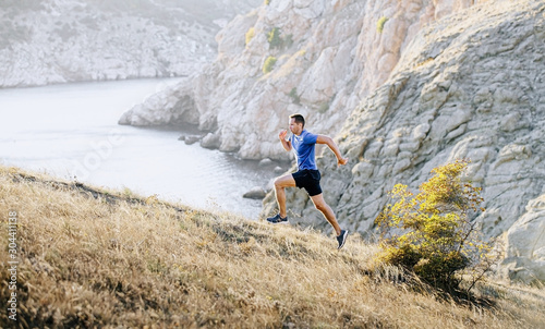 Fotografie, Obraz man athlete dynamic running uphill on background mountain and sea bay