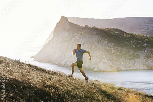 Fotografie, Obraz sporty man running mountain trail in uphill at sunset and sunlight