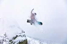 Elite Snowboarder Frozen At The Moment Of The Jump. Girl Freerider Jumping Off A Cliff In A Remote Taiga In A Snowstorm. Poor Visibility And Heli Skiing