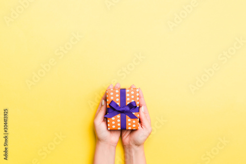Cuadros en Lienzo  Woman arms holding gift box with colored ribbon on yellow table background, top