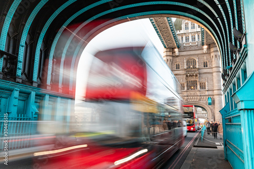 Tower bridge in London with blurred red bus and tourists