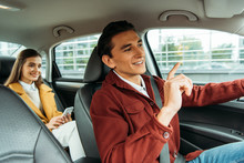 Smiling Taxi Driver And Passenger With Smartphone In Car