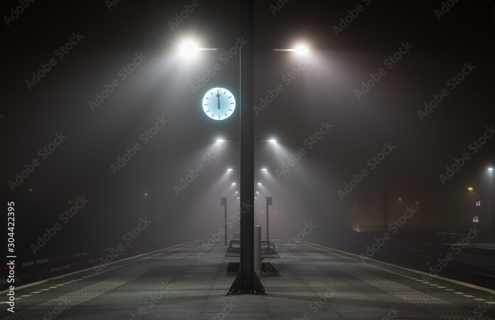 Fototapety, obrazy: Illuminated, empty platform at a railroad station during a foggy night in autumn.