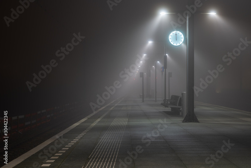 Photo Illuminated, empty platform at a railroad station during a foggy night in autumn