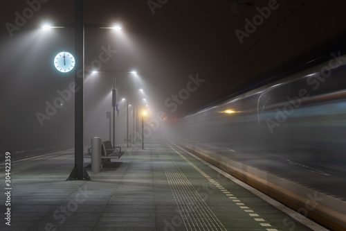 Fotomural Train passing an empty platform at a railroad station during a foggy evening