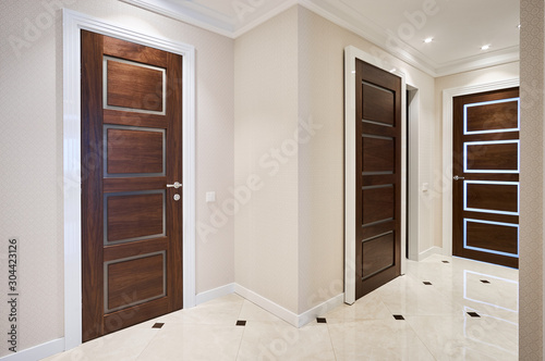 The door is made of walnut wood in a classic style with white architraves in the Wallpaper Mural