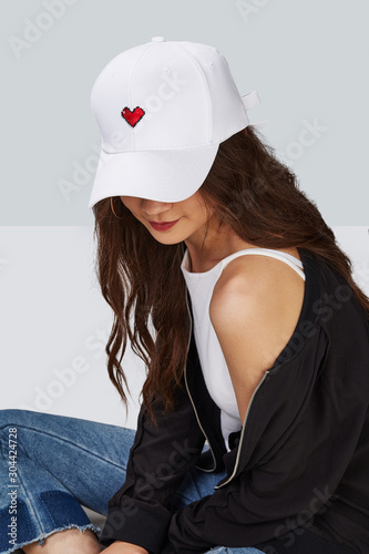Cropped upward shot of a dark-haired girl, wearing white baseball cap with heart print, white tank top and black jacket Fototapeta