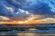 sunset in the cloudy sky over the stormy sea on the sandy shore