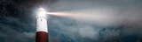 Large lighthouse with bright search light on a dark and stormy night panoramic