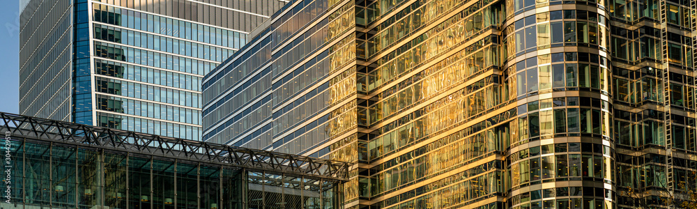 Fototapeta Modern city building architecture with glass fronts on a clear day at sunset in London, England panoramic