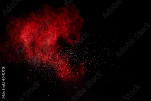 Red powder explosion on black background. Freeze motion of red dust particles splash. - 304429708