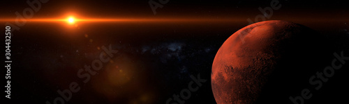 Sunrise over the planet mars in space with strong flare and shadows panoramic - 304432510