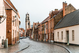 Fototapeta Uliczki - Ancient streets of the old city of Brugge in Belgium. An empty street from a lumber block extending into the distance in rainy weather.