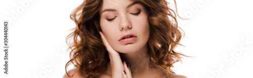 panoramic shot of beautiful young woman with closed eyes touching face isolated on white