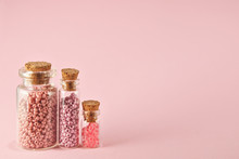 Beige, Purple, Orange And Yellow Beads In Glass Jars On A Bright Pink Background. Beads In A Transparent Container With A Wooden Cork. The Concept Of Orderliness, Balance And Chaos.