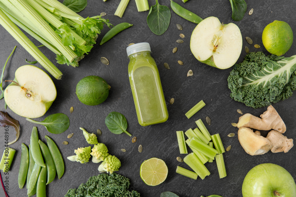 Fototapeta healthy eating, food and vegetarian diet concept - bottle of fresh green juice or smoothie, fruits and vegetables on slate stone background
