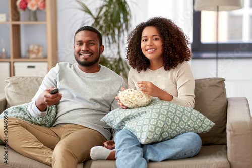 Fotografie, Obraz  people and leisure concept - african american couple with popcorn watching tv at
