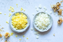 Yellow And White Cosmetic Beeswax Pellets In White Ceramic Bowl For Homemade Natural Beauty And D.I.Y. Project.