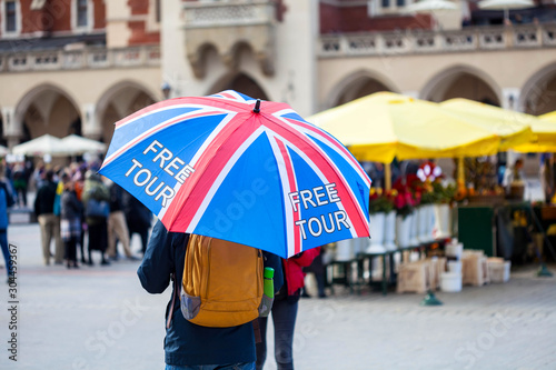Fototapeta Free tour on a Cracow market square, a UK english guide with a united kingdom flag umbrella seen from the back. Local free of charge tourist guides. Tourism, travelling for england residents concept obraz