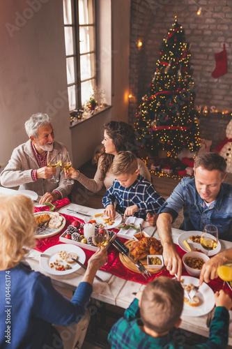 Foto Family celebrating Christmas at home, having dinner